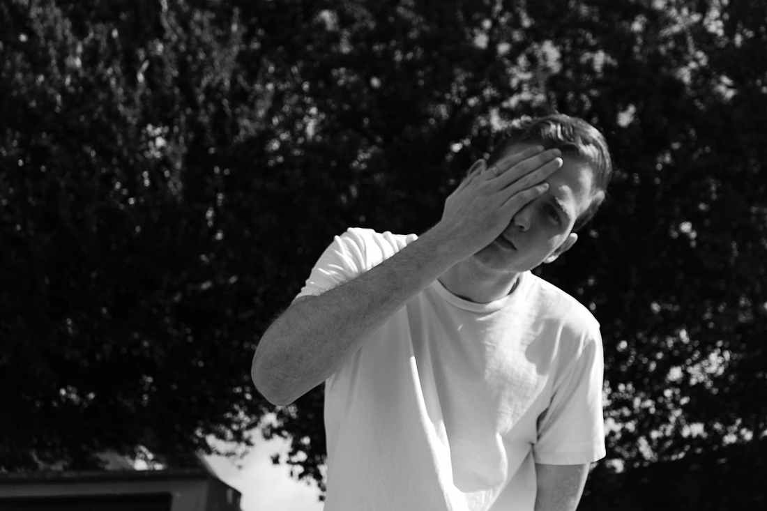 grayscale photo of man wearing white crew neck shrit